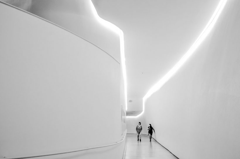 two-woman-walking-near-white-building-959323